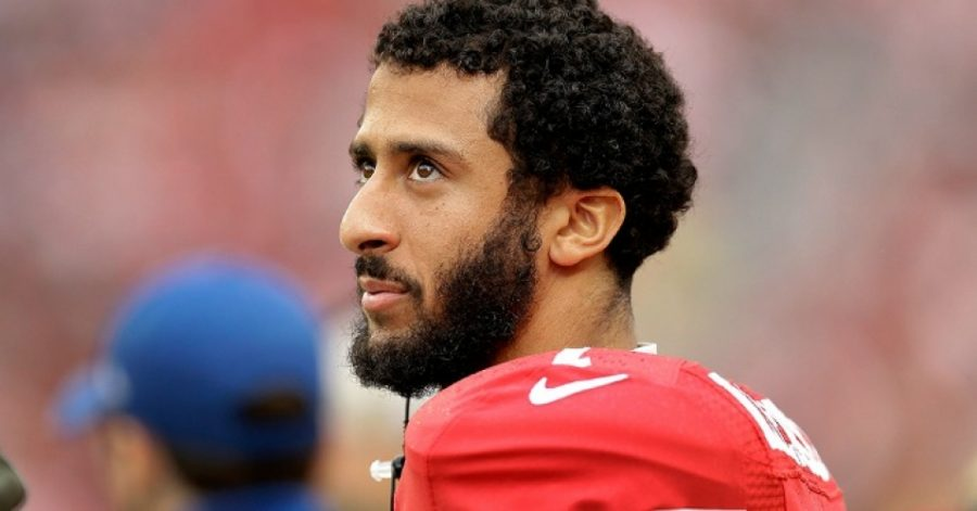 During+a+NFL+football+game%2C+Colin+Kaepernick%2C+49ers+Quarterback%2C+sat+down+during+the+Pledge+of+Allegiance+as+a+protest.+