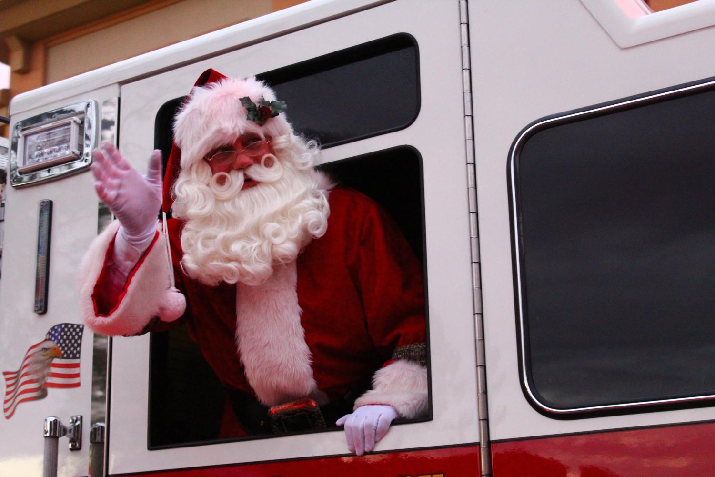Santa waves to parade spectators on the street.